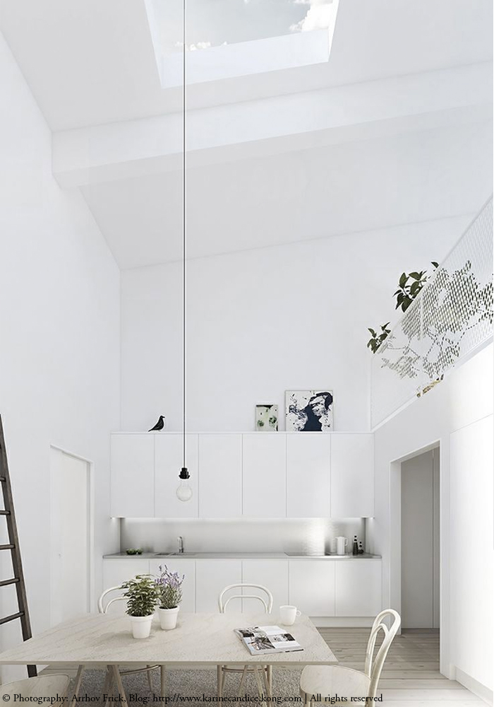 A minimalist white kitchen with high ceiling