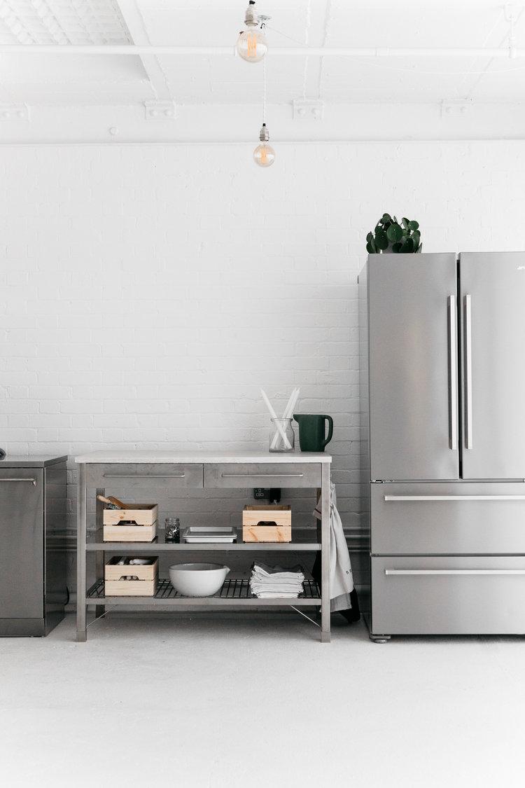 A white industrial kitchen with Smeg appliances